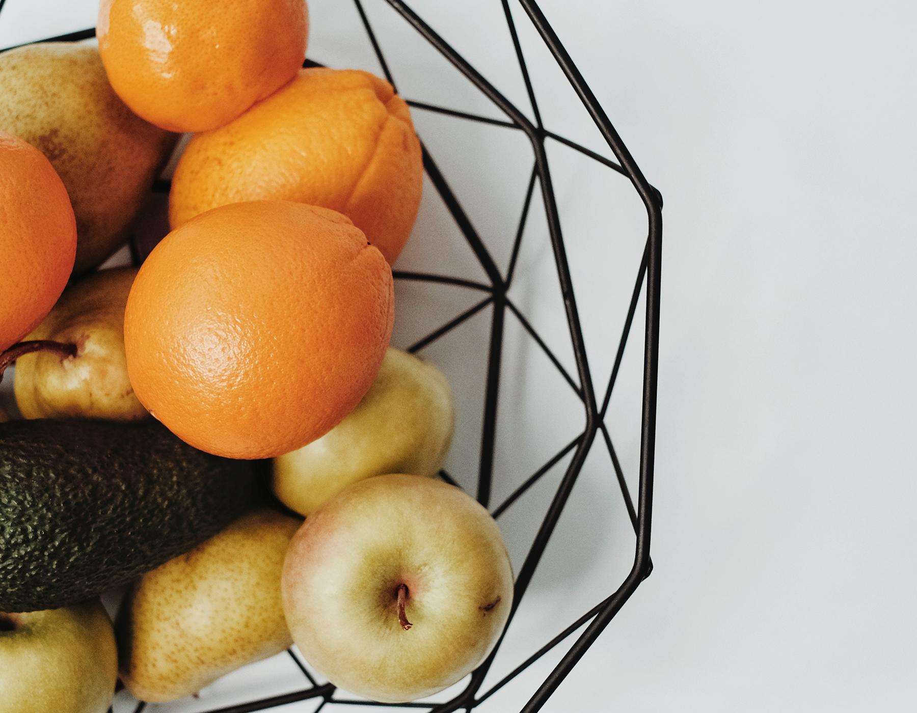 Een fruitmand vol sinaasappels, appels en peren.